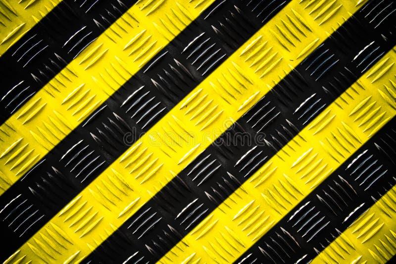 Waarschuwingsbord gele en zwarte die strepen over de plaat van de staalcontroleur of diamantplaat op de vloer als textuurachtergr stock afbeelding