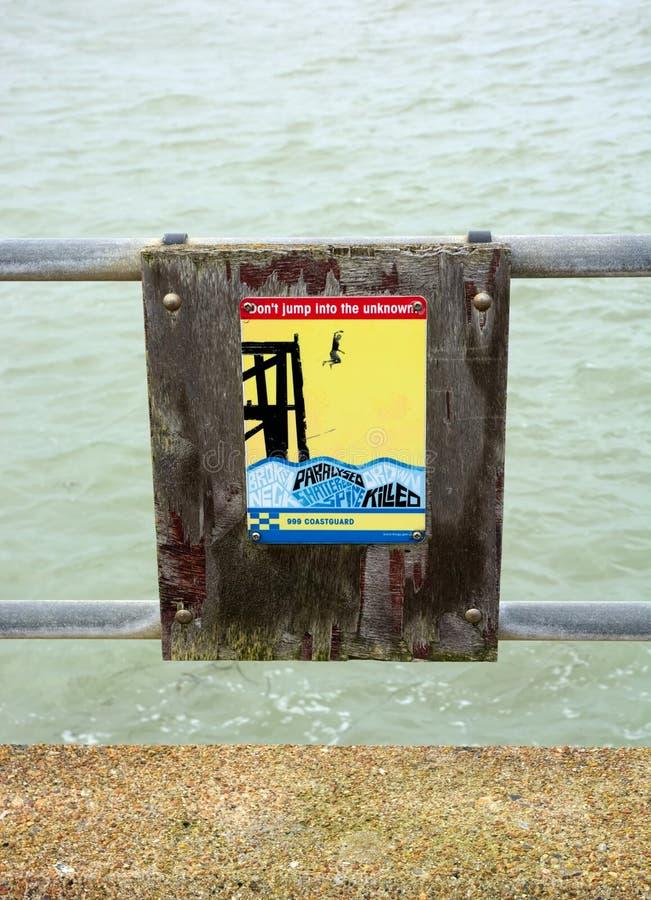 Waarschuwingsbord op havenmuur stock afbeeldingen