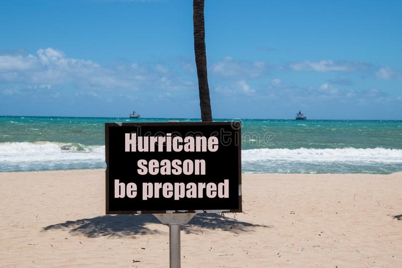 Waarschuwingsbord op strand naast de boomstam van een palm op een zonnige dag met een blauwe duidelijke hemelwaarschuwing dat het stock fotografie