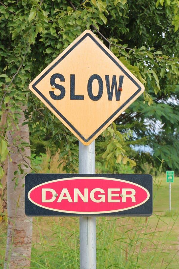Waarschuwingsbord van langzaam, om de snelheid en het gevaar te verminderen stock foto