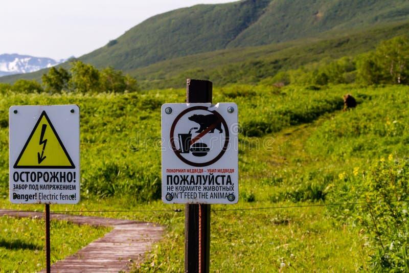 Waarschuwingsborden op de omheining: 'Voed niet de dieren! 'en 'Gevaar! Elektrische omheining! 'in Russische en Engelse talen Kro stock foto's
