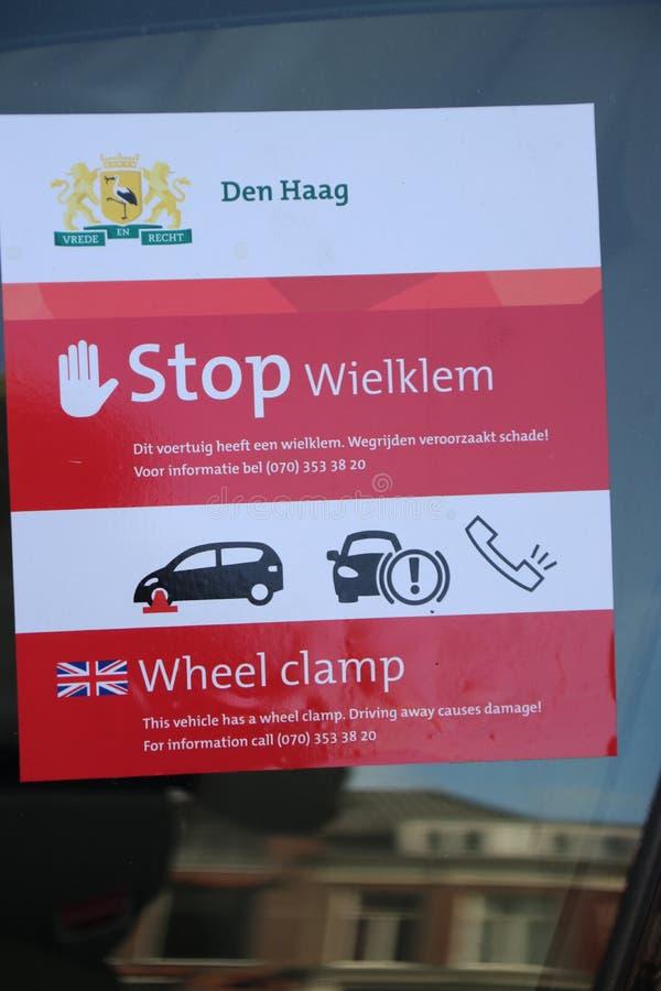 Waarschuwingssticker op het voorvenster van een auto die de handhaving van de gemeente van Den Haag stock afbeelding