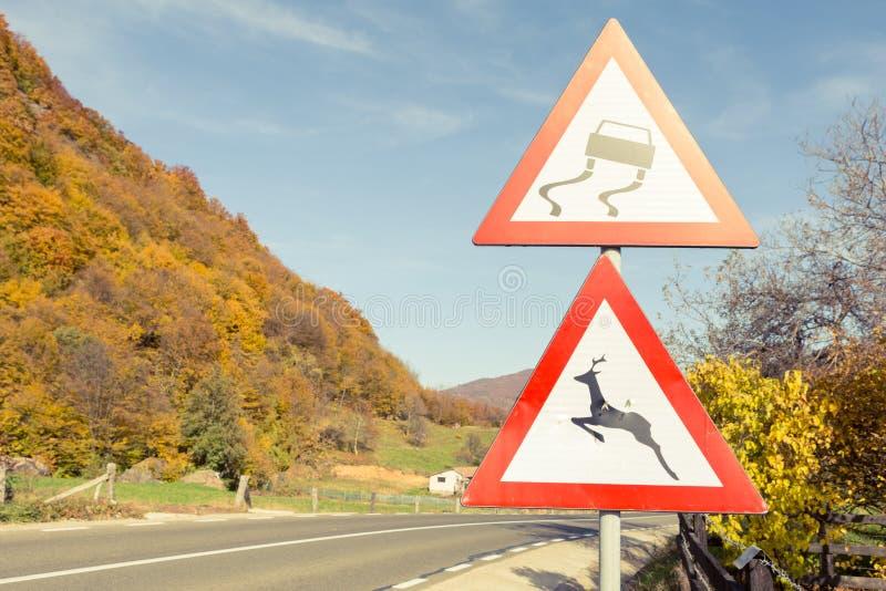 Waarschuwingsverkeersteken over gladde weg en wilde dieren stock fotografie