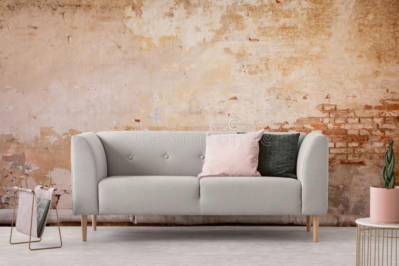 Wabi sabi living room interior with old shabby wall and trendy new couch with pastel pink and black pillows, real photo.  stock image