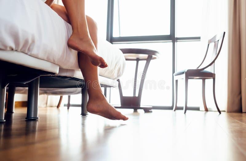 Wachen Sie Frau - nahe hohe Bildfrauenbeine im Schlafzimmer auf stockbilder