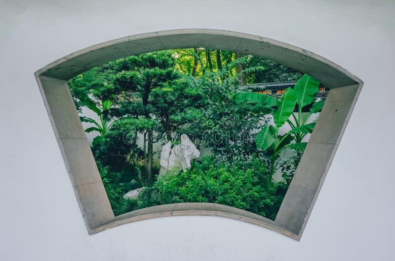 Wachlarzowaty nadokienny otwarcie na białej ścianie z widokiem drzewa i skała, w tradycyjni chińskie ogródzie blisko Zachodniego  fotografia royalty free