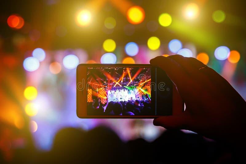 Wachluje brać fotografię koncert przy festiwalem smatphone zdjęcie stock
