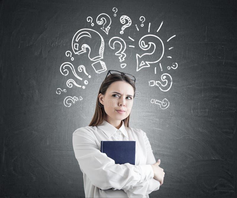 Wachsame Frau mit einem Buch, viele Fragen lizenzfreies stockbild