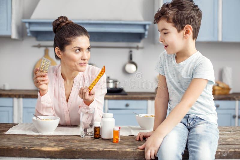 Wachsame Mutter, die über Vitamine mit ihrem lieben Sohn spricht stockfoto