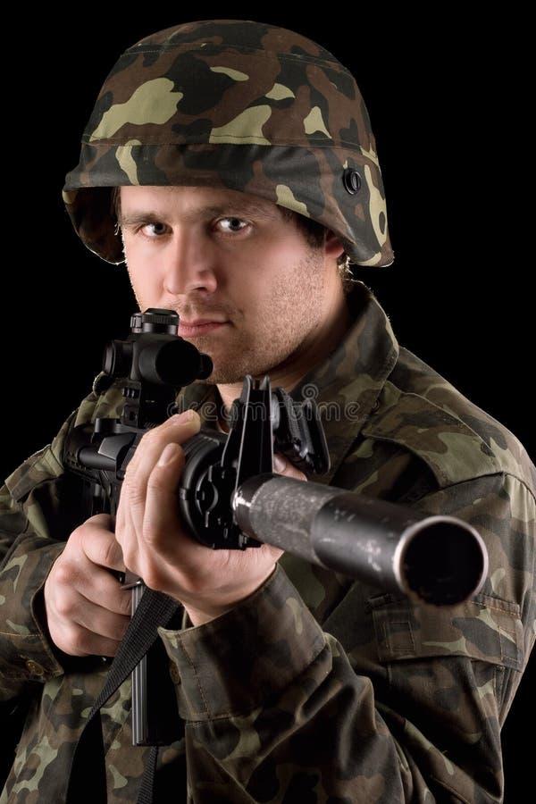 Wachsamer Soldat, der m16 im Studio zielt stockfotos