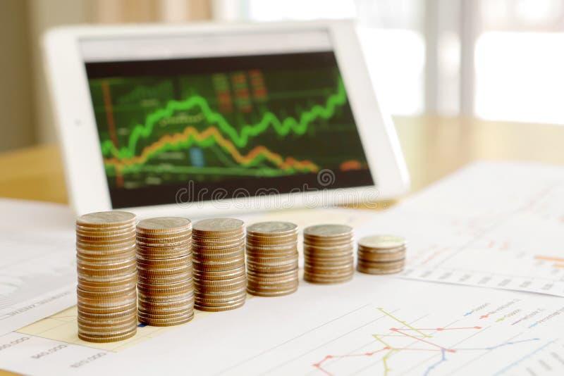 Wachsen Sie Münzenstapel mit Geschäft heran und finanzieren Sie Diagrammschirm stockfotografie