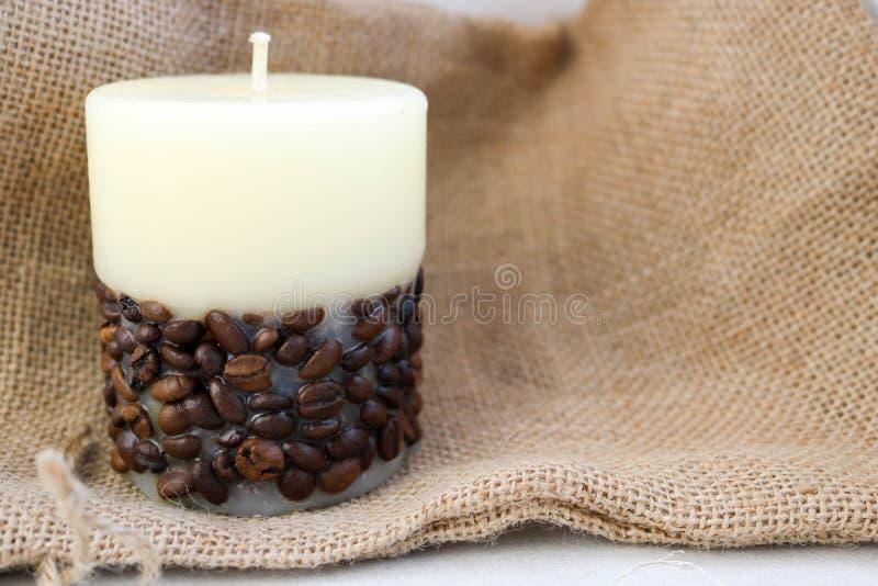 Wachsen Sie schöne helle beige Kerze mit dem unflavored Docht ein von unterhalb, der mit Kaffeebohnen auf dem Hintergrund des alt lizenzfreies stockbild