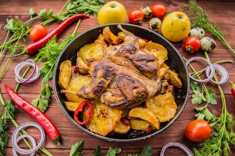 Wachteln backten in einer Wanne mit Kartoffeln und Äpfeln Auf braunem hölzernem Hintergrund Beschneidungspfad eingeschlossen Naha lizenzfreies stockfoto