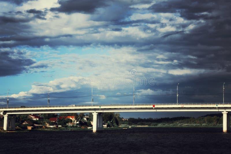 Wachten op de regen Sunlit brug over de rivier Prestormwolken rond stock fotografie