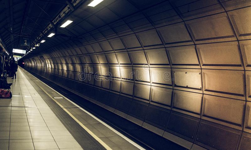 Wachtend in mooi station houdt de tunnel geen trein bij het aankomen Heathrow luchthaven, Londen tegen Spoorweg met het uitsteken stock afbeelding