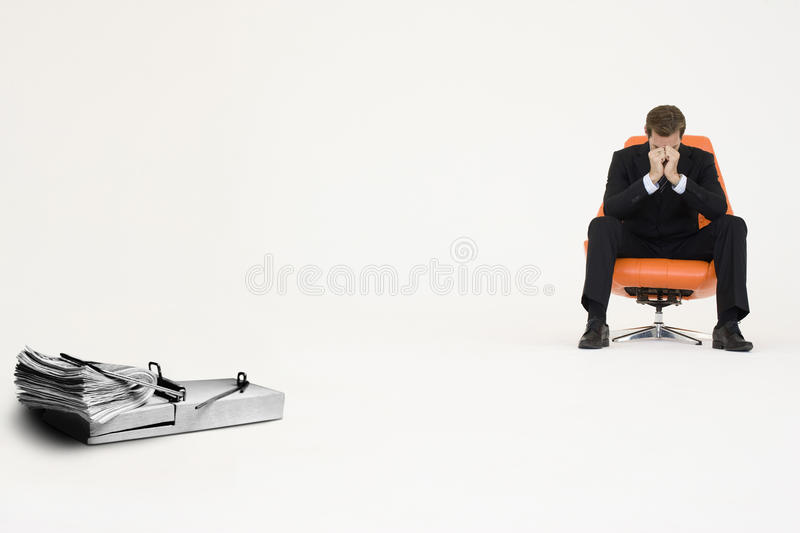Wad of cash on mouse trap with worried businessman sitting on chair representing financial difficulties royalty free stock images