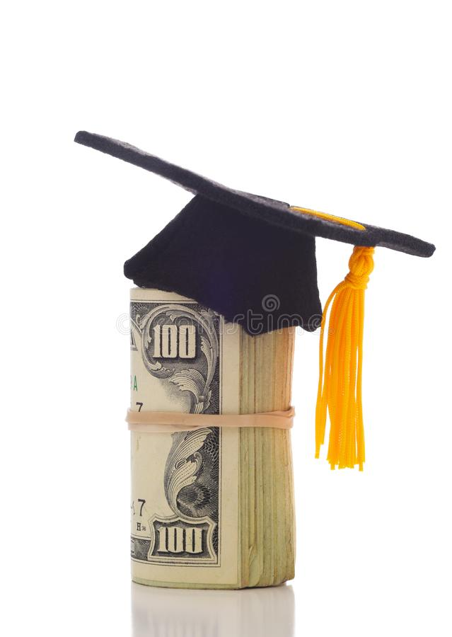 A wad of hundred dollar bills wrapped around themself with a mortarboard ontop depicting  the College Admission Bribery Scandal. A wad of hundred dollar bills royalty free stock photo