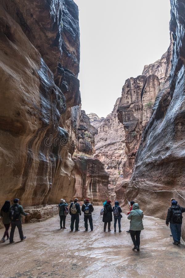 Numerous tourists walk along the canyon leading to Petra - the capital of the Nabatean kingdom in Wadi Musa city in Jordan. Wadi Musa, Jordan, December 06, 2018 royalty free stock photography