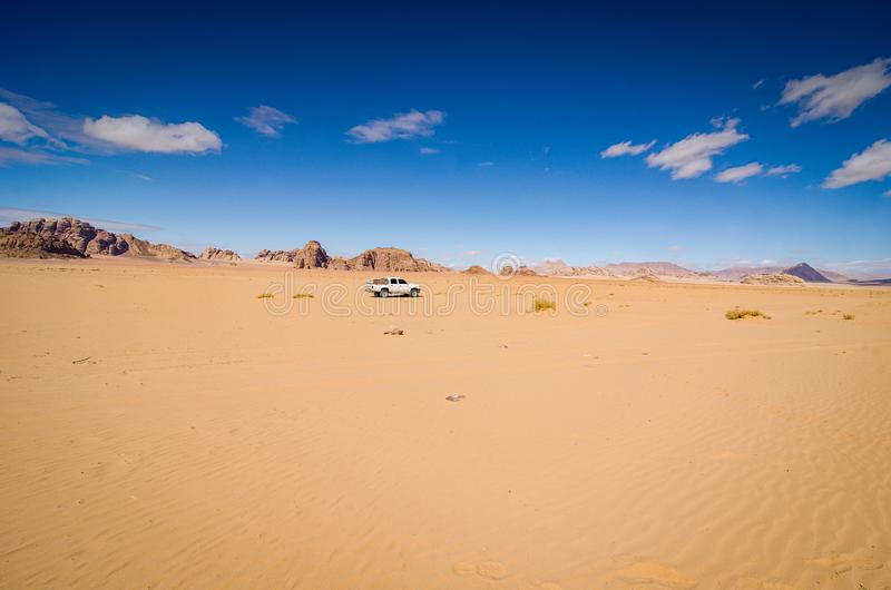 Wadi Rum, Jordan - January 26, 2016. Desert of Wadi Rum with offroad car in the middle.  royalty free stock photos