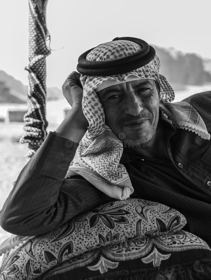 """Wadi Rum, Jordanië †""""20 Juni, 2017: Bedouin mens of de Arabische mens in traditionele uitrusting, die op de laag liggen, verlaa stock fotografie"""