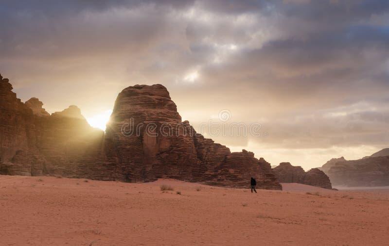 Wadiego rumu pustyni krajobraz w wschód słońca mężczyzna chodzi samotnie w wadiego rumu pustyni w Jordania, Środkowy Wschód fotografia royalty free