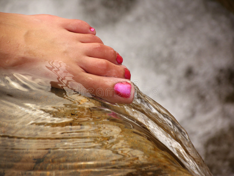 Wading. Woman's foot on the edge of a waterfall
