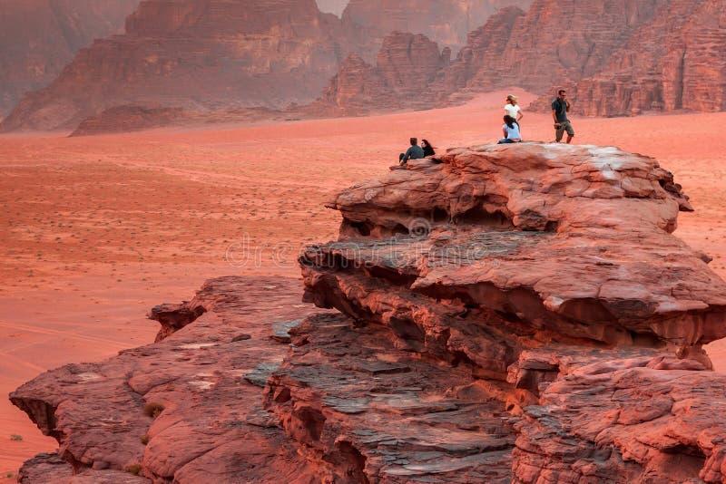 WADIrum, JORDANIË - MEI 11, 2013: Onbekende mensen die van het mooie landschap van de woestijn van Wadi Rum van een kleine klip g stock afbeelding