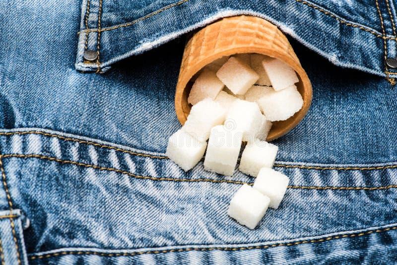 Wafelkegel met geraffineerde suiker op denimachtergrond Kegelhoogtepunt van geraffineerde suiker in zak van jeans Kegel voor room stock foto's