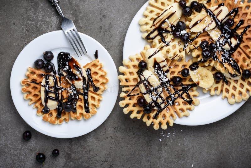 Wafels met chocolade, banaan en bessen stock foto's
