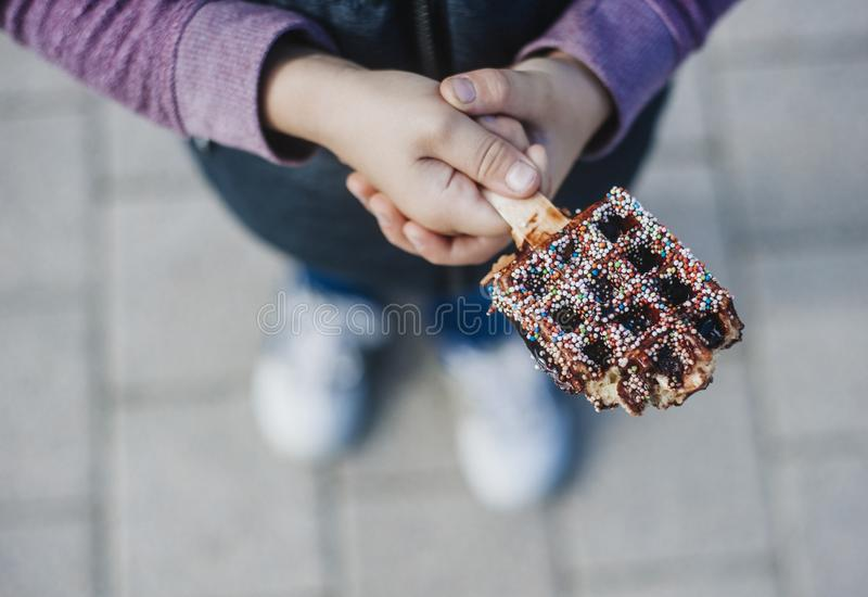 Wafels met chocolade in jonge geitjeshanden Belgische Wafels royalty-vrije stock afbeelding