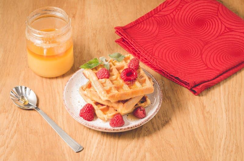Wafels met framboos in plaat op een rood servet/wafels met framboos in plaat op een rood servet, en kruik honing op houten stock afbeelding