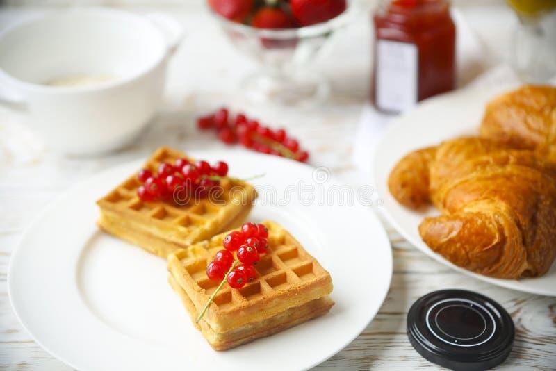 Wafels met rode aalbesjam en bessen, croissants, oranje jui stock afbeelding