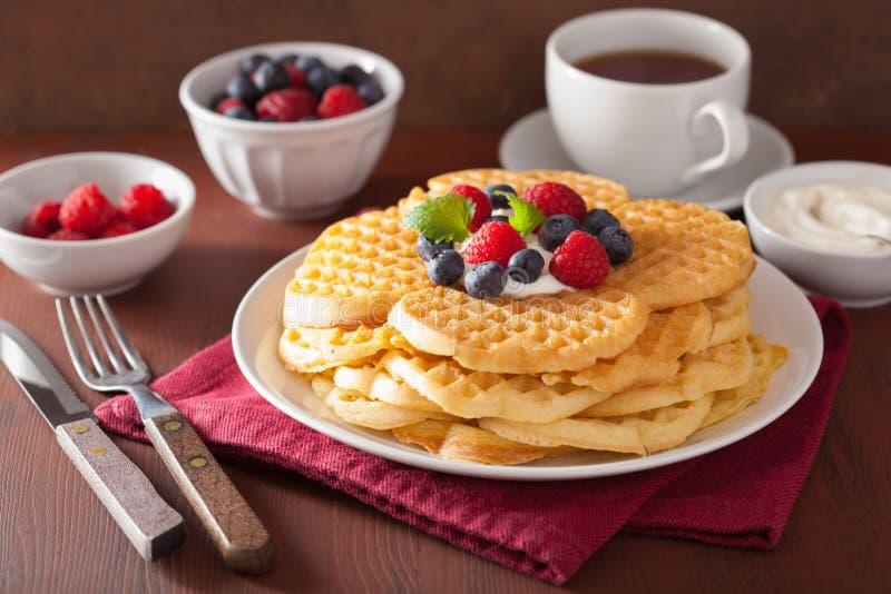 Wafels met room fraiche en bessen voor ontbijt stock afbeelding