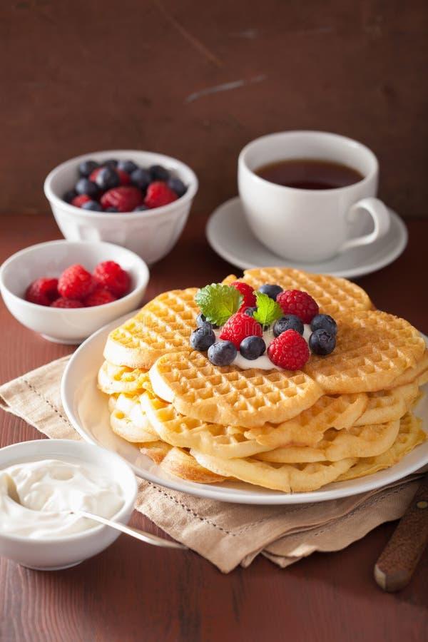 Wafels met room fraiche en bessen voor ontbijt stock afbeeldingen