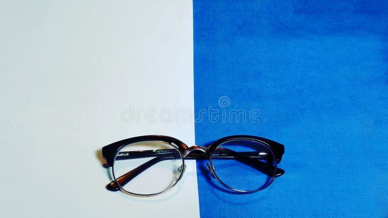 Wafeltje glasses_specs op blauwe en witte achtergrond stock fotografie