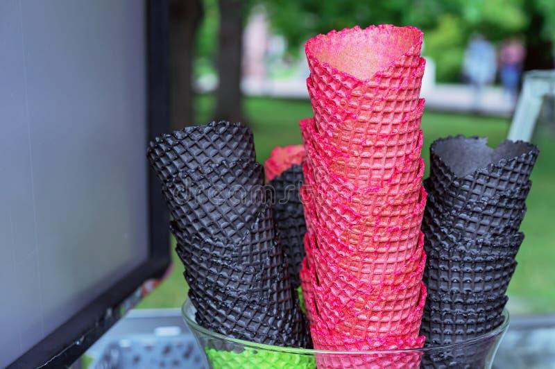 Wafeltjekoppen voor roomijs van rode en zwarte kleuren Wafelkegels op de teller van een roomijsverkoper royalty-vrije stock foto