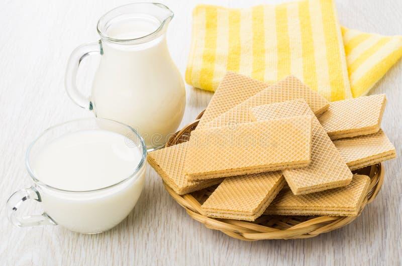 Wafeltjes in rieten mand, waterkruik en kop met melk, servet royalty-vrije stock afbeelding