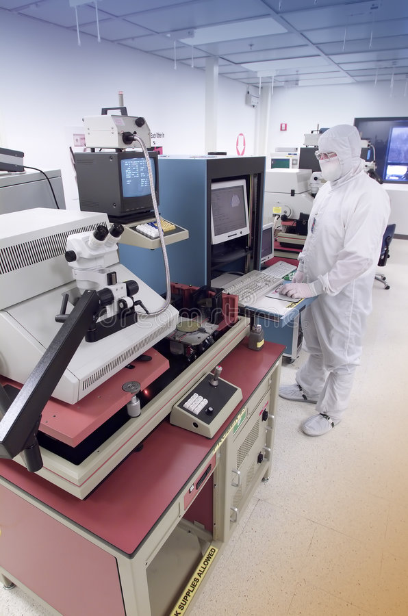 Wafer analysis lab. Technician operating computer on wafer quality control equipment in clean room royalty free stock image