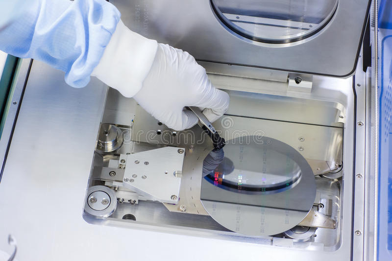Wafer handling inside a cleanroom. Handling of a silicium wafer inside a cleanroom. Placing the wafer into the loadlock of an atomic layer depositioning machine stock images