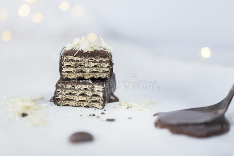 Wafer with melted chocolate sauce and white chocolate sprinkles, close up, stock photo