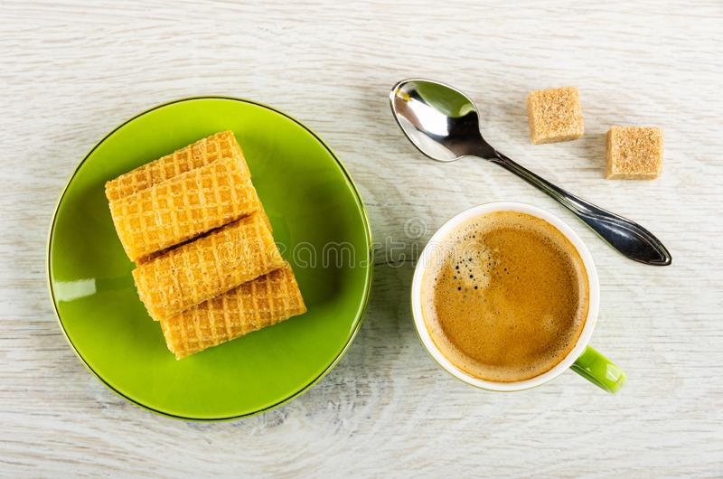 Wafer rolls in saucer, spoon, sugar, cup with coffee on table. Top view. Wafer rolls in saucer, spoon, sugar cubes, green cup with coffee espresso on light royalty free stock photos
