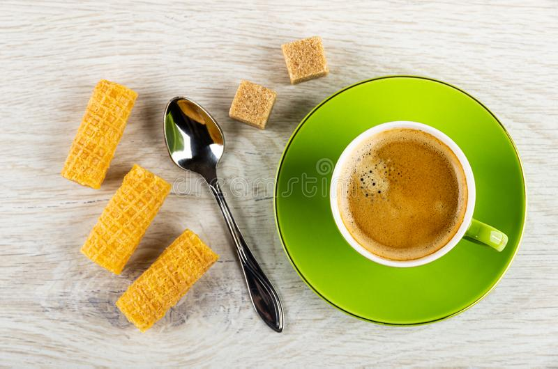 Wafer rolls, spoon, sugar, cup with coffee on saucer on wooden table. Top view. Wafer rolls, spoon, sugar cubes, green cup with coffee espresso on saucer on royalty free stock photo