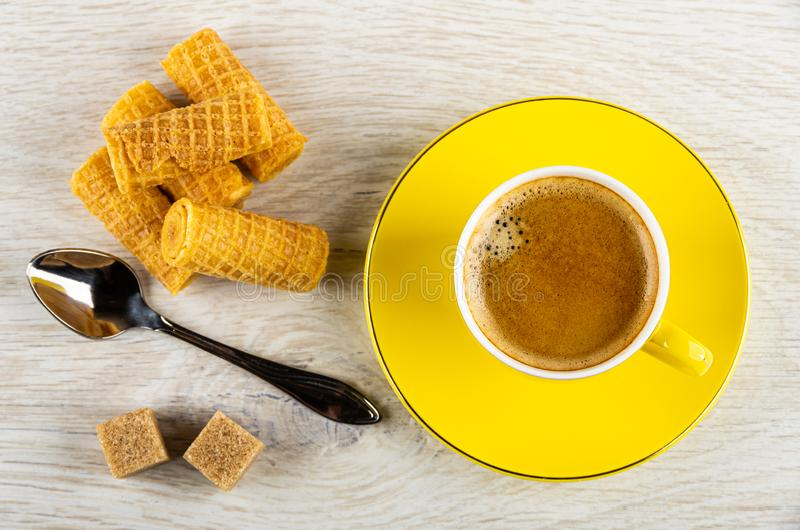 Wafer rolls, spoon, sugar, yellow cup with coffee on saucer on wooden table. Top view. Heap of wafer rolls, spoon, sugar cubes, yellow cup with coffee espresso stock image