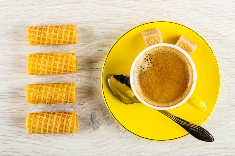 Wafer rolls, yellow cup with coffee, spoon, sugar on saucer on table. Top view. Row of wafer rolls, yellow cup with coffee espresso, spoon, sugar cubes on saucer royalty free stock photography