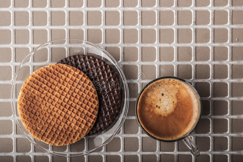 Wafers with cup of coffee on the relief background top view royalty free stock image