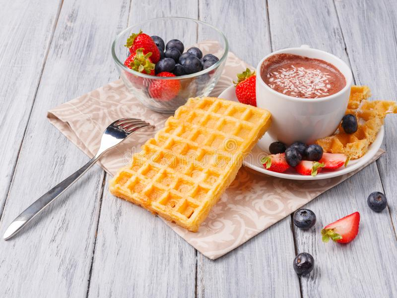 Wafers with fruits and berries on a close-up table. Waffles with a side of a drink and a bowl of strawberries and blueberries. Everything on a towel and a gray royalty free stock photography