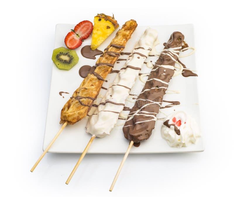 Waffel-Stöcke tauchten mit der Schokolade, Früchten und Schlagsahne ein, die auf Weiß lokalisiert wurden stockbilder