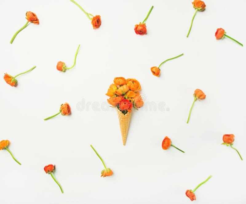 Waffelkegel mit orange Butterblume blüht über weißem Hintergrund, Flachlage stockfotos