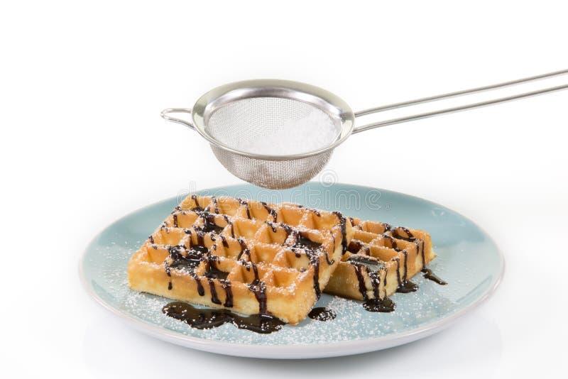 Waffeln mit Schokolade auf einer bläulichen Platte Etwas Puderzucker I stockbild