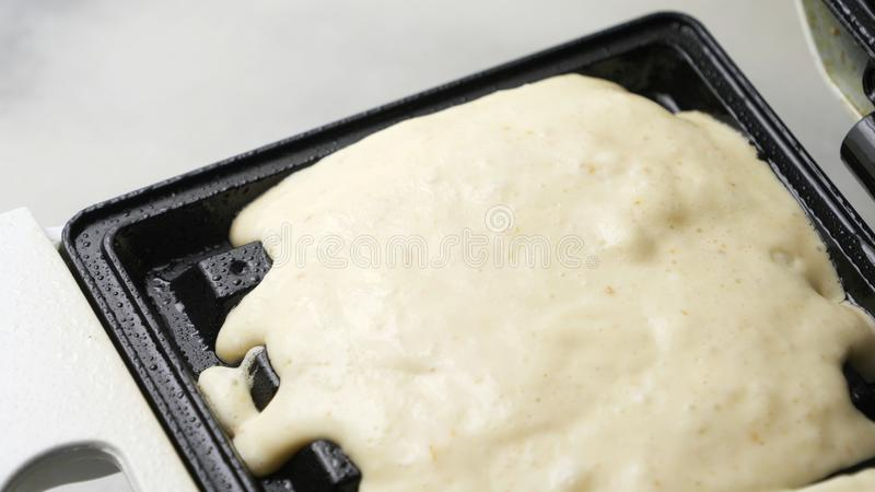 A waffle being made.Waffle batter being poured on a waffle iron royalty free stock images